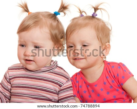 Two little girls are watching an invisible object; isolated on the white background - stock photo