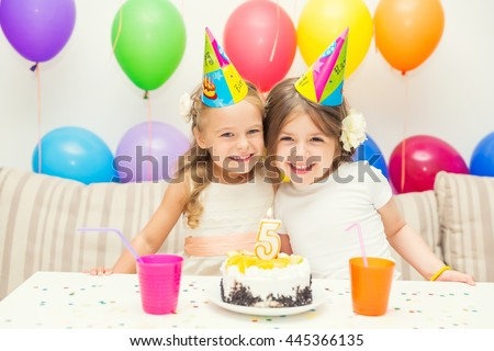 Two little girls at birthday party - stock photo