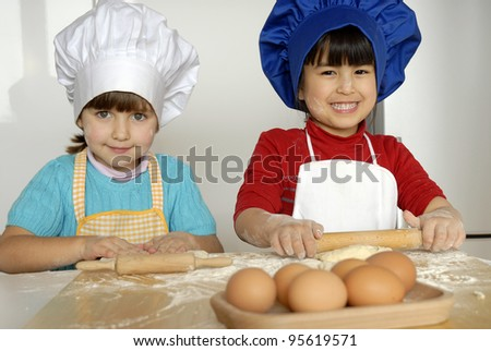 Two Little girls cooking a pizza in a kitchen.Little kid in a kitchen together. - stock photo