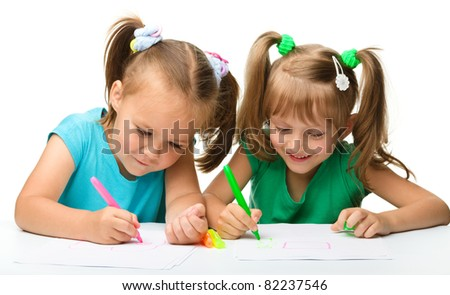 Two little girls draw with markers while sitting at table, isolated over white