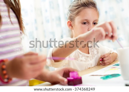 Two little girls drawing pictures