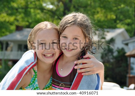 two little girls embrace after swimming on a summer day - stock photo