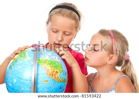 two little girls exploring a globe - stock photo