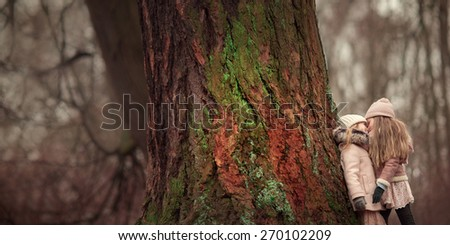 two little girls friends with long blond hair in coats and hats are standing and looking at each other near the big tree in the forest - stock photo
