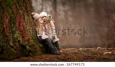 two little girls friends with long blond hair in coats and hats are standing arms in arms and hugging near the big tree in the forest  - stock photo