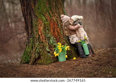two little girls friends with long blond hair in coats and hats with yellow flowers in the cans near them are standing arms in arms and hugging near the big tree in the forest  - stock photo