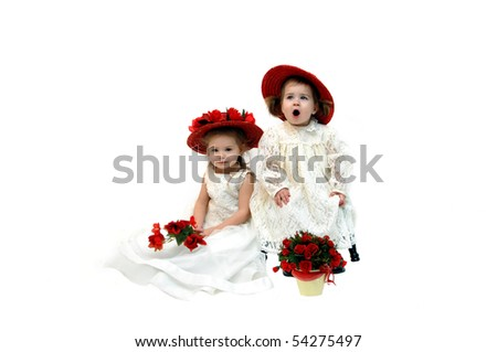 Two little girls from the country dress up in lacy dresses and fancy hats camouflaging their country roots.  But two cute pigtails pop out from under the toddler's red straw hat. - stock photo