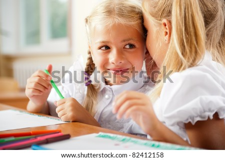 Two little girls gossip in classroom