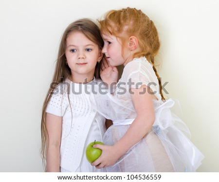 Two little girls gossiping. - stock photo