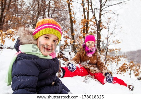 Two little girls having fun in winter - stock photo
