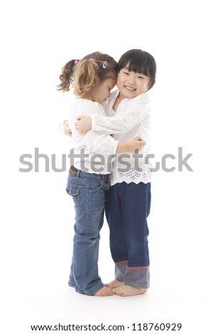 Two little girls hugging each other. Studio shot against a white background. - stock photo