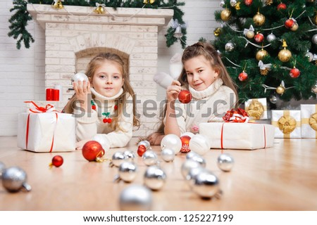 Two little girls in a room with Christmas gifts