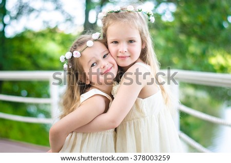 Two little girls in beautiful dresses and tiaras with flower in the hair hugging in the park on a sunny summer day. - stock photo