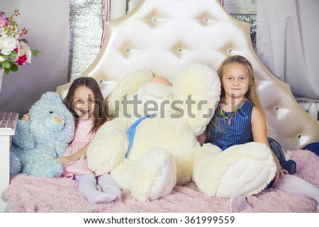 Two little girls in bed with soft toys