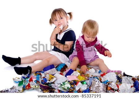 Two little girls in candy wrappers from sweets - stock photo
