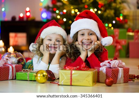 Two little girls in the Santa hat with the Christmas gift under the tree - stock photo