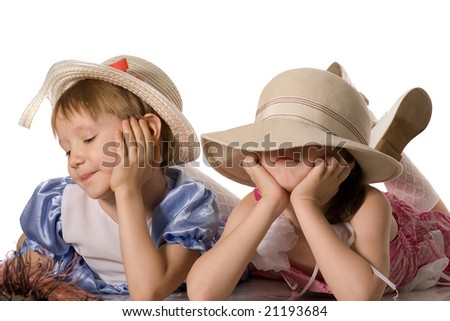 Two little girls lie on the floor, turned away, isolated on white - stock photo