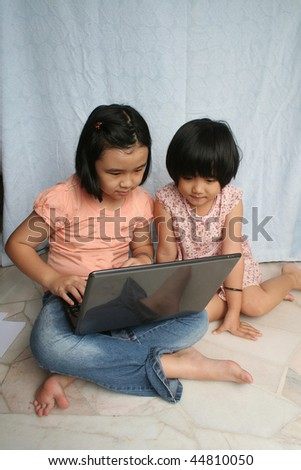 Two little girls looking and using the laptop