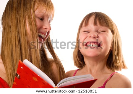 Two little girls looking like sisters holding red book, laughing, isolated on white background - stock photo