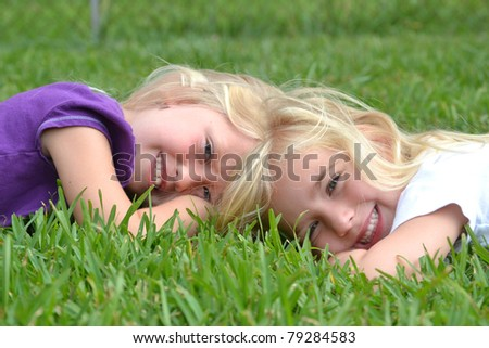 two little girls lying in the grass - stock photo