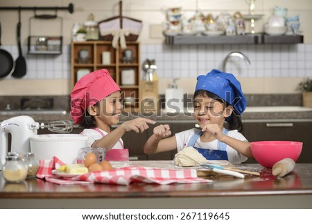 Two Little Girls Make Pizza In The Kitchen - stock photo