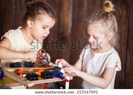 Two little girls making very interesting creations with tools and wood at home