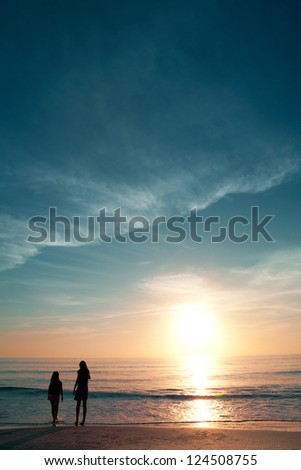 Two little girls on beautiful beach during sunset. - stock photo