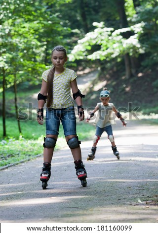 Two little girls on inline skates in park - stock photo