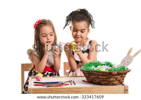 Two little girls painting  Easter eggs isolated on white background - stock photo