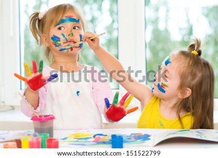two little girls painting with paintbrush and colorful paints - stock photo