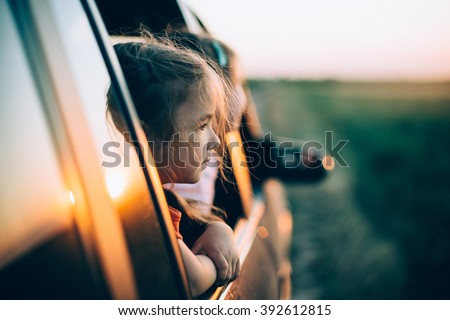 Two little girls peeks out of the car in the sunset - stock photo