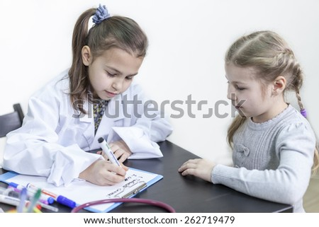 Two little girls playing doctor and patient - stock photo
