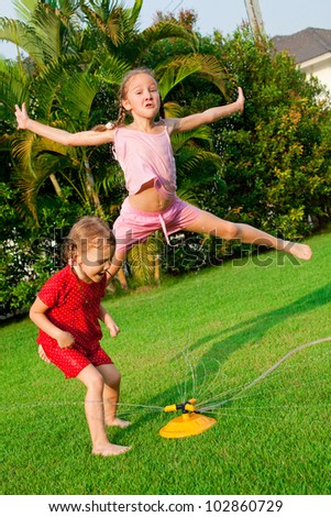 two little girls playing in the garden - stock photo
