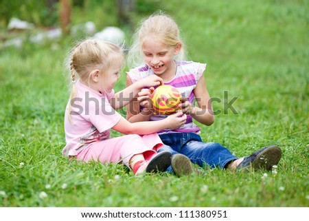 Two little girls playing in the grass  with the ball