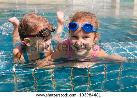 two little girls playing in the pool - stock photo