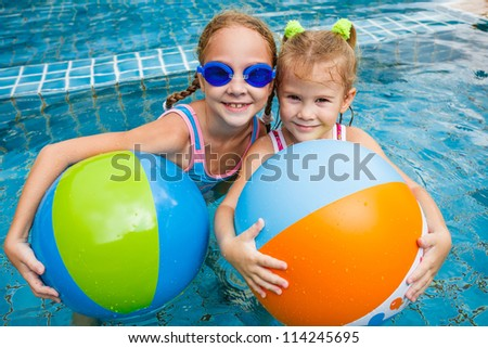 two little girls playing in the pool with balls