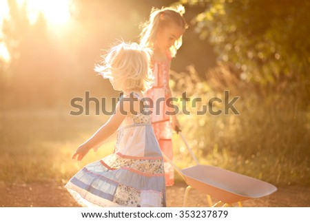 Two little girls playing in the sun - stock photo