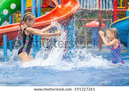 two little girls playing in the swimming pool - stock photo