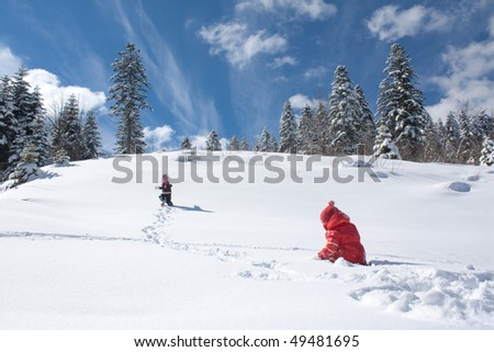 two little girls playing on the snow - stock photo