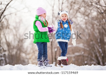 Two little girls playing snowballs