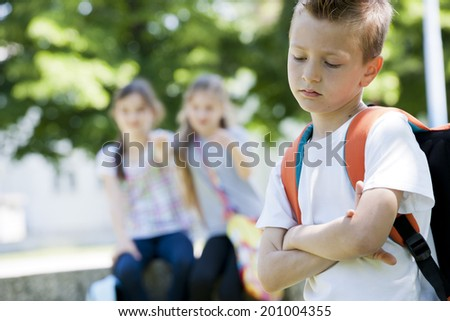 Two little girls poting at the little sad boy, focus on foreground - stock photo