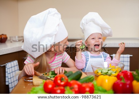 two little girls preparing healthy food on kitchen