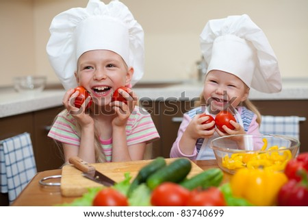 two little girls preparing healthy food on kitchen (left girl is focused) - stock photo