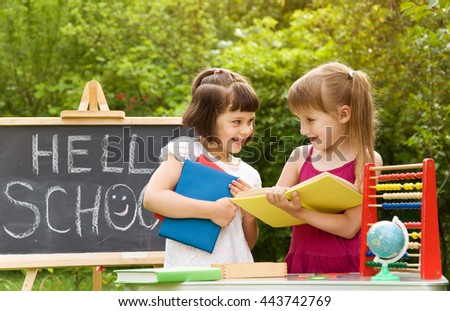 Two little girls reading a book on the nature and talking - stock photo