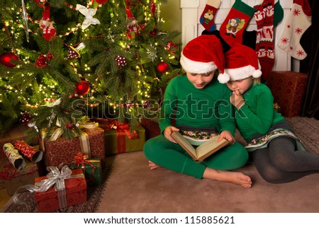 Two little girls reading in a book near the christmas tree