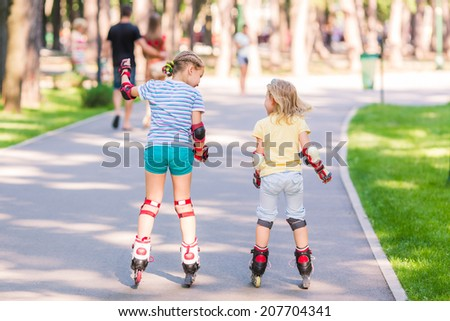 Two little girls rollerskating in the park outdoor