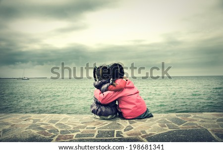 Two little girls sitting near the sea - stock photo