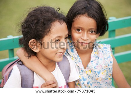 two little girls sitting on a bench in the playground