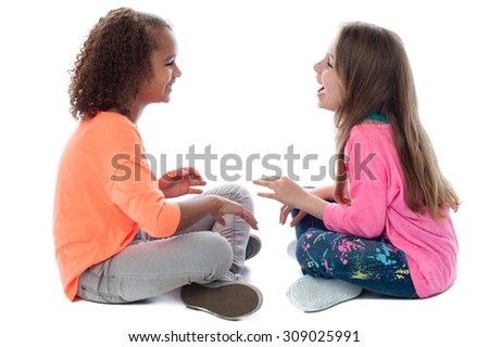 Two little girls sitting on floor and playing - stock photo