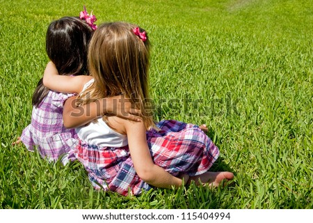 Two little girls sitting on grass